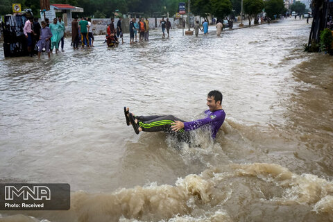 مردی هنگام عبور از یک خیابان آب گرفته هنگام باران موسمی در کراچی ، پاکستان