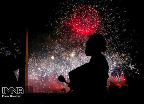یک معترض در حال تماشای انفجار آتش بازیهای انتخاباتی ترامپ