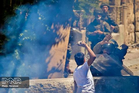 یک تظاهرکننده فلسطینی در جریان اعتراض در کرانه باختری به سمت سربازان اسرائیلی سنگ پرتاب می کند