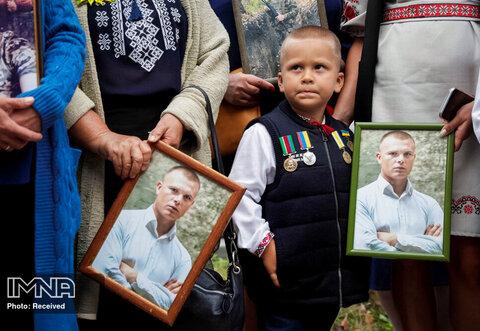 نزدیکان پرتره هایی از یک سرباز اوکراینی را که در درگیری در شرق اوکراین کشته شده است ، در بزرگداشت ششمین سالگرد نبرد ایلوائیسک در کیف ، اوکراین در دست دارند