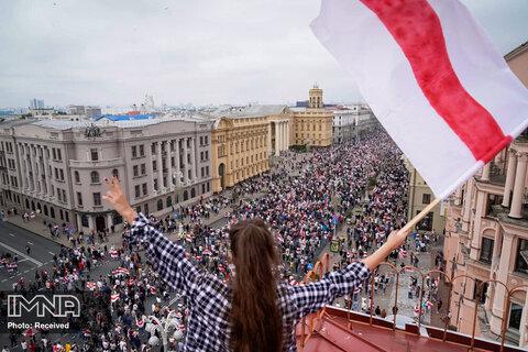 یک زن با پرچم بلاروس در جمع معترضان
