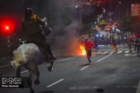 تظاهرکنندگان در حالی که پلیس سوار آنها را در جریان اعتراض به بی رحمی پلیس در مدلین، کلمبیا تعقیب می کنند ، می دوند