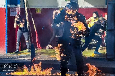 هنگام درگیری با تظاهرکنندگان معترض به وحشیگری پلیس در کلمبیا ، یک بمب بنزین به یک افسر پلیس ضد شورش پرتاب شده است