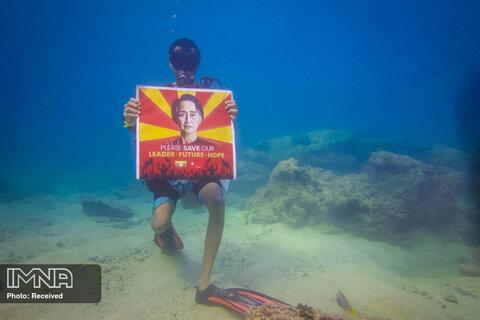 غواص معترض به همراه پلاکارد آنگ سان سوچی