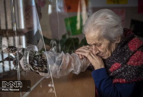 یکی از ساکنان خانه سالمندان در هنگام شیوع بیماری کرونا، دخترش را از طریق یک صفحه پلاستیکی بغل می کند.ایتالیا