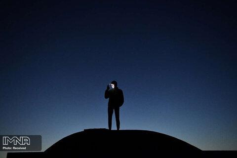 بازتاب نور موبایل بر صورت یک مرد هنگام تماشای غروب در بندر دان لائوگر دوبلین در ایلند
