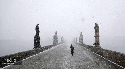 عبور یک زن از روی پل قرون وسطایی چارلز هنگام بارش برف در پراگ، جمهوری چک