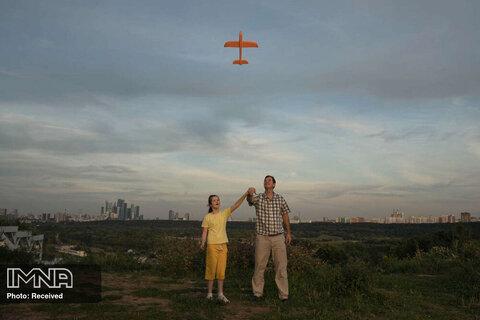 رتبه سوم تک تصویر پرتره آموزش یک پدر روسی به دختر مبتلا به اوتیسم خود برای به پرواز درآوردن هواپیمای اسباب بازی