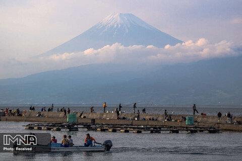 نمای کلی کوه فوجی ، بلندترین کوه ژاپن با ارتفاع 3776 متر در حالی که مردم در نومازو ، استان شیزوئوکا ماهیگیری می کنند.