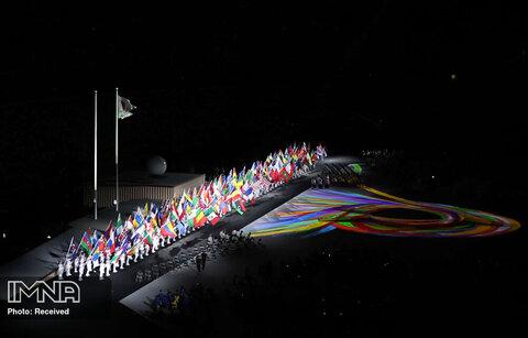 داوطلبان پرچم های ملی کشورهای مختلف را هنگام آغاز رژه ورزشکاران در مراسم افتتاحیه به نمایش گذاشتند